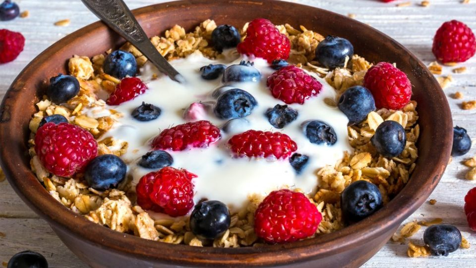 bowl of oat granola with yogurt, fresh raspberries, blueberries and nuts with spoon